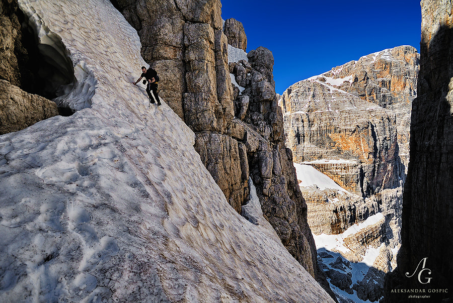 Traversing snow covered walls of the deep gorge below the Campanile Basso on the Via Delle Bocchette ferrata trail in the Brenta Dolomites.