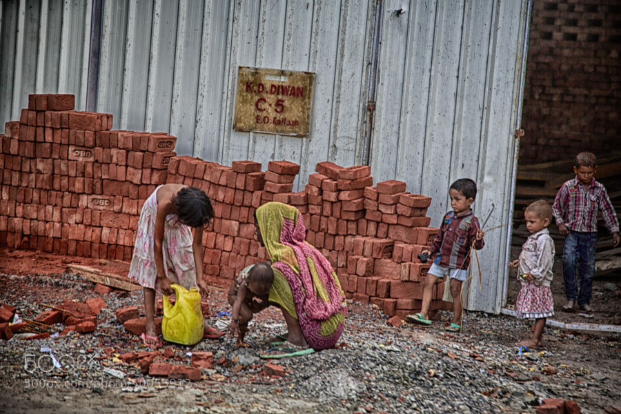 Digital color image of woman and children at a brick pile (Delhi, India)
