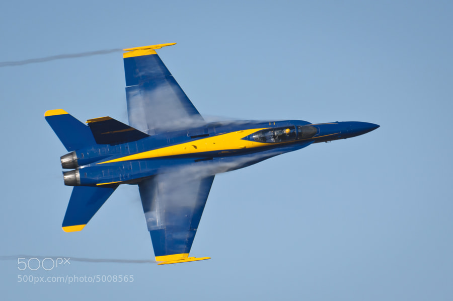 Blue Angels F/A-18C Hornet streams vapor from its wings as it enters a hard right turn.