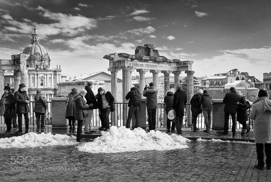 Tourists brave the first snowfall in Rome for twenty-six years to take in the ancient sights of the Forum