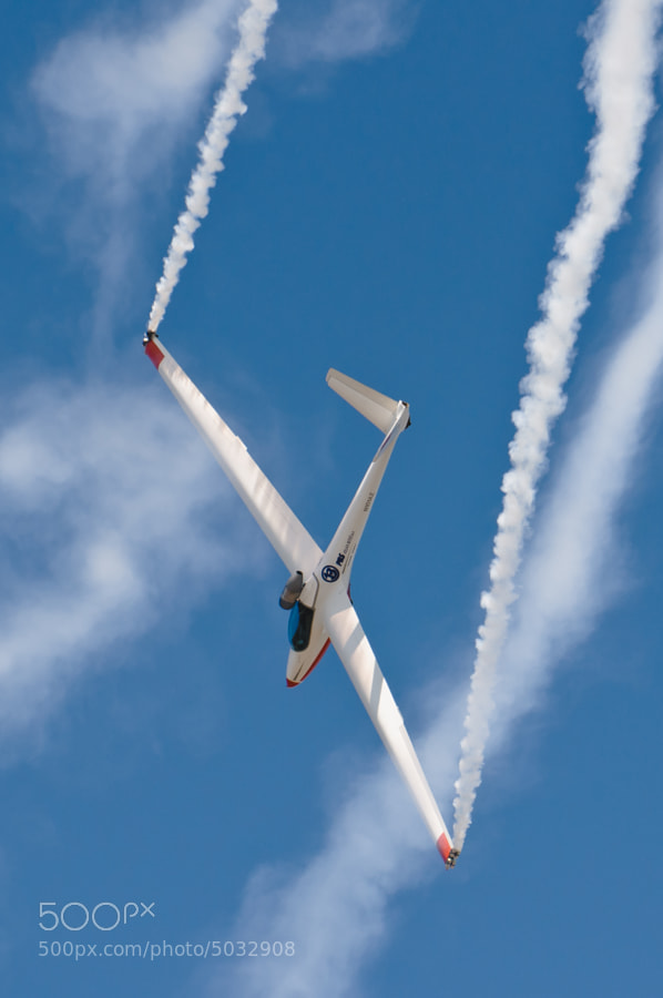A jet powered glider soars through its own smoke trail over NAS Pensacola