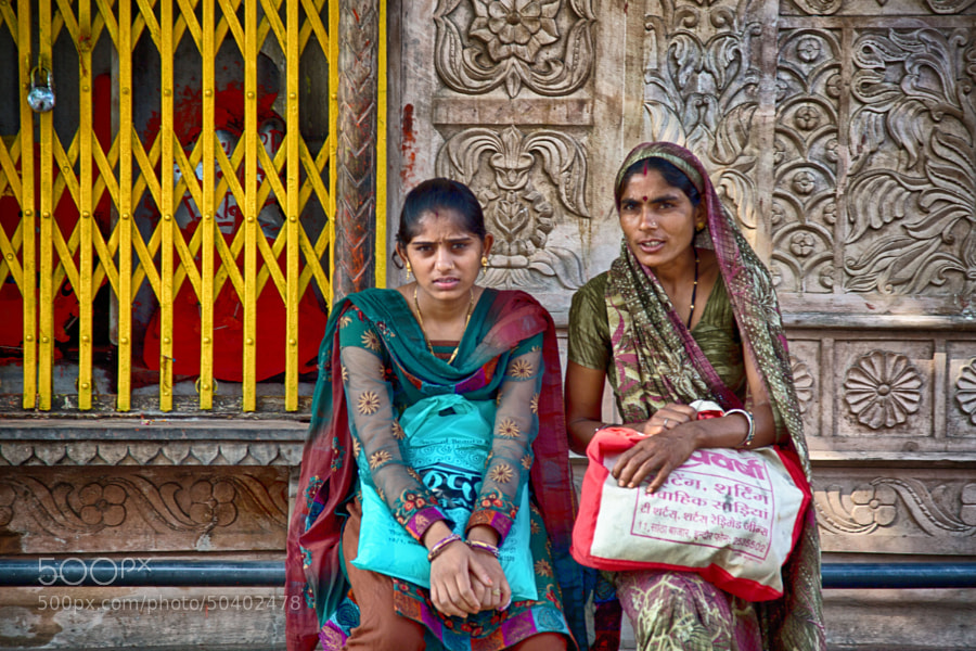 Digital color image of two ladies with shopping bags seated on a street corner in Indore, India