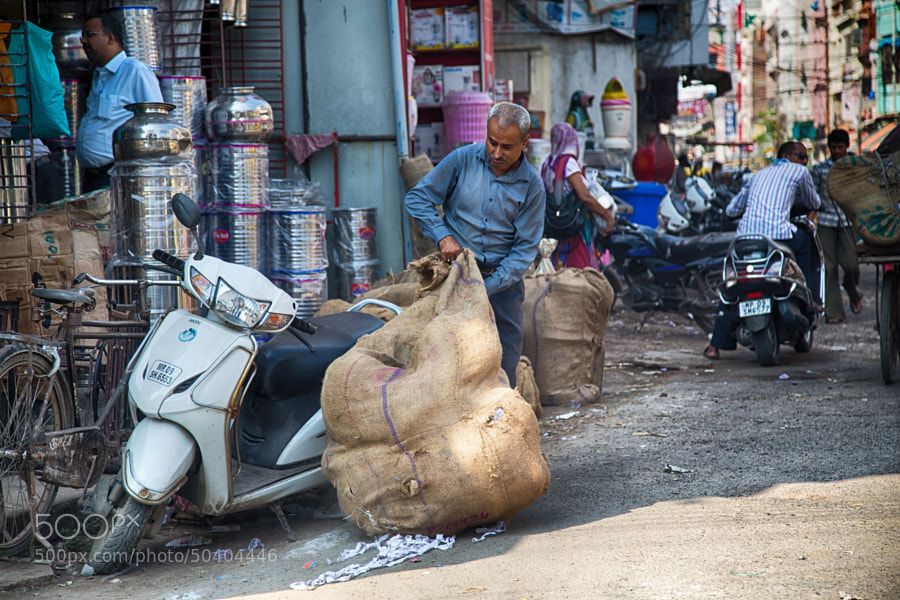 Digital color image of man on a street corner in Indore (India) attempting to load a huge sack onto his scooter.