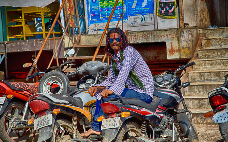 Digital color image of long-haired dude wearing blue shades sitting on a motorcycle (Indore, India)