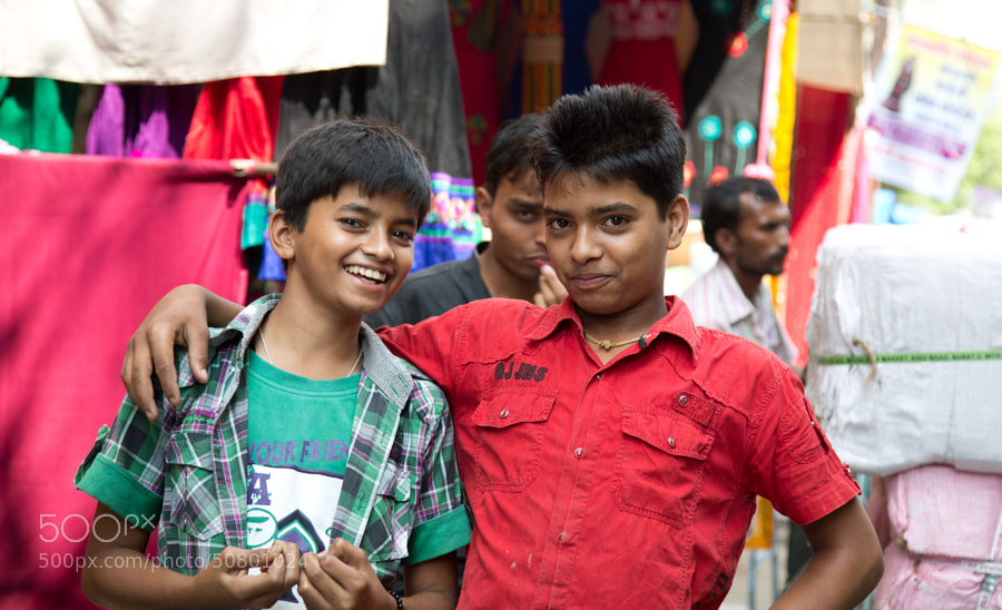 Digital color image of two young boys posing for the camera at the marketplace in Indore, India