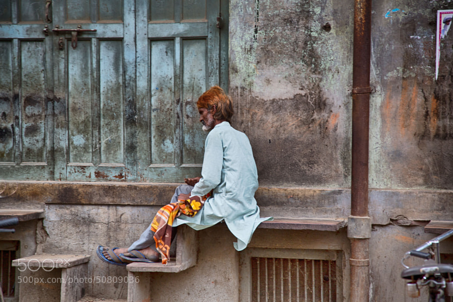 Digital color image of a man resting on a ledge outside of a  building on a street corner near the cloth market in Indore, India