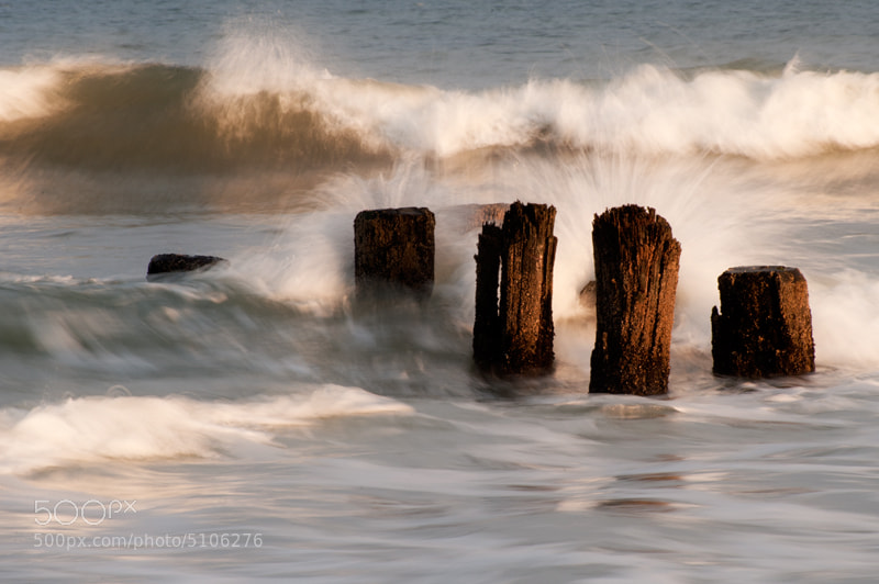 Surf breaking on old pier pilings at Carolina Beach, NC in afternoon light.
