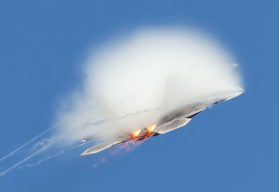 An F-22 Raptor, with afterburners on, creates a vapor cloud