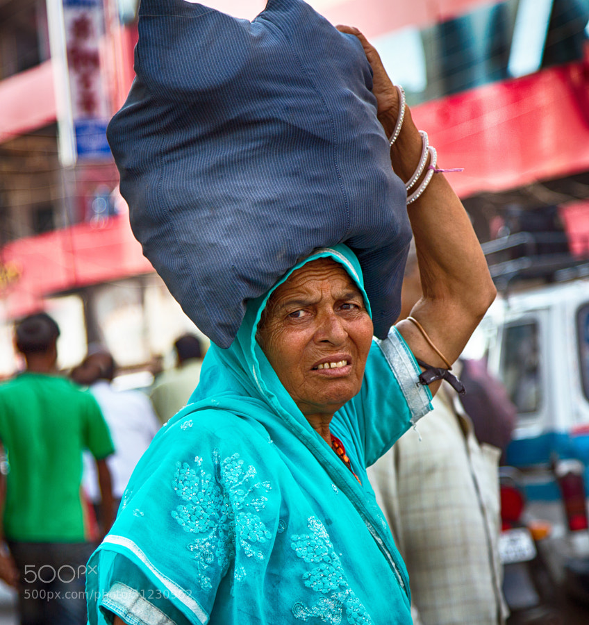 Digital color image of a woman with a grimaced face, carrying a large sack on her head on a street corner in Indore, India
