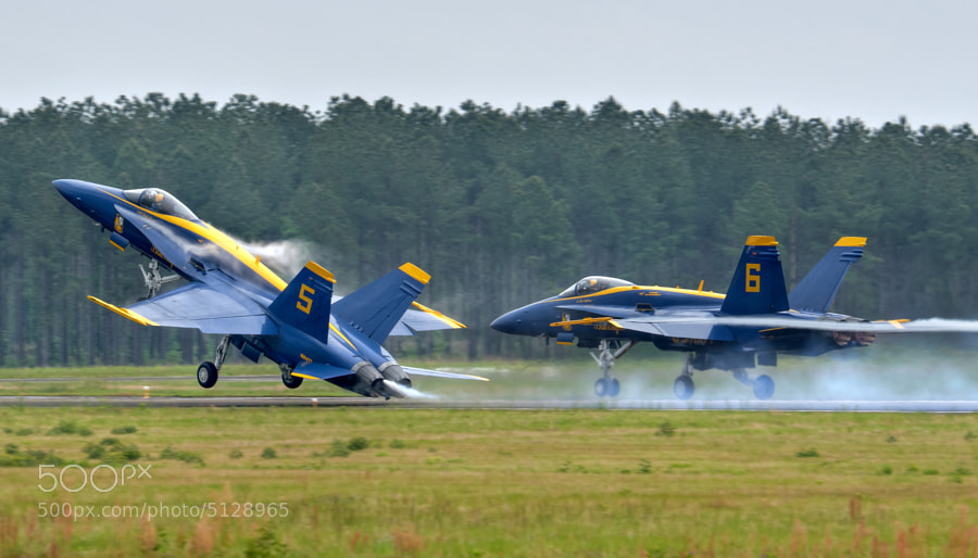Vapor trails from the wings of Blue Angels 5 & 6 as they takeoff during a steady rain at Vidalia, Georgia.