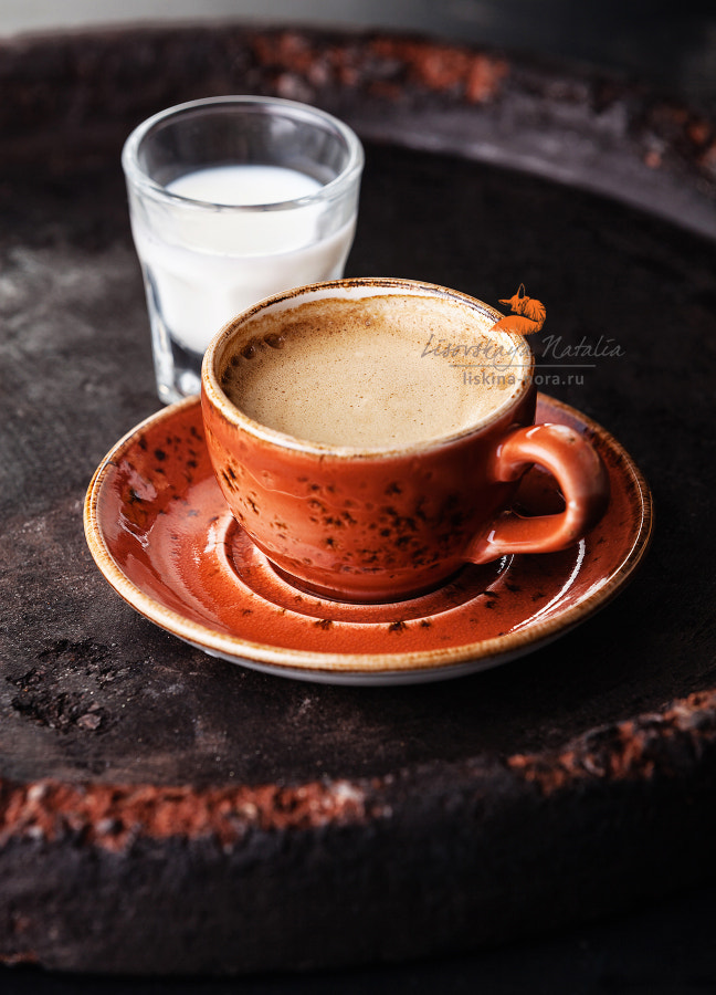 Cup of espresso coffee with milk on dark background