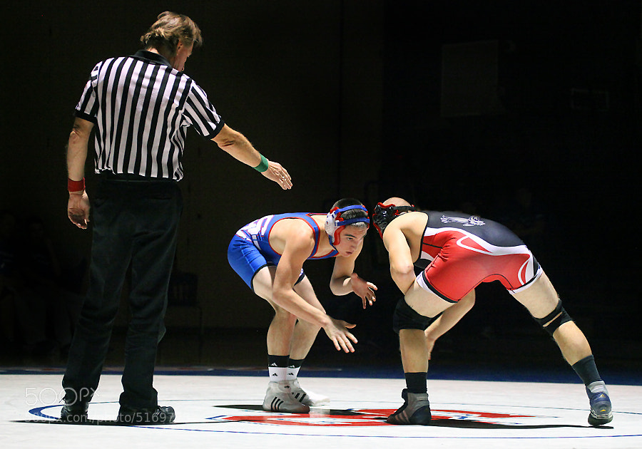 A pair of grapplers prepare to face off in a high school wrestling match.