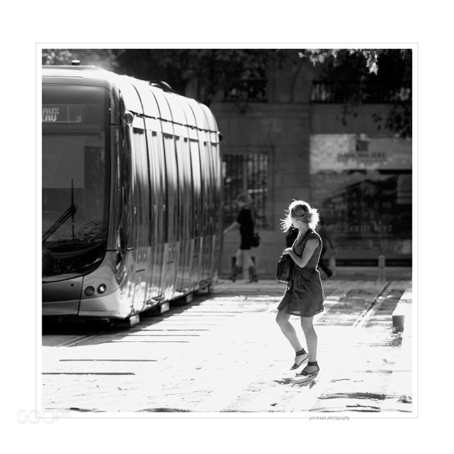 Crossing the tracks at one of the tram stops at Place Quinconces on a warm summer afternoon in Bordeaux (France). This is one of the places in town that are buzzing with activity during most of the day.