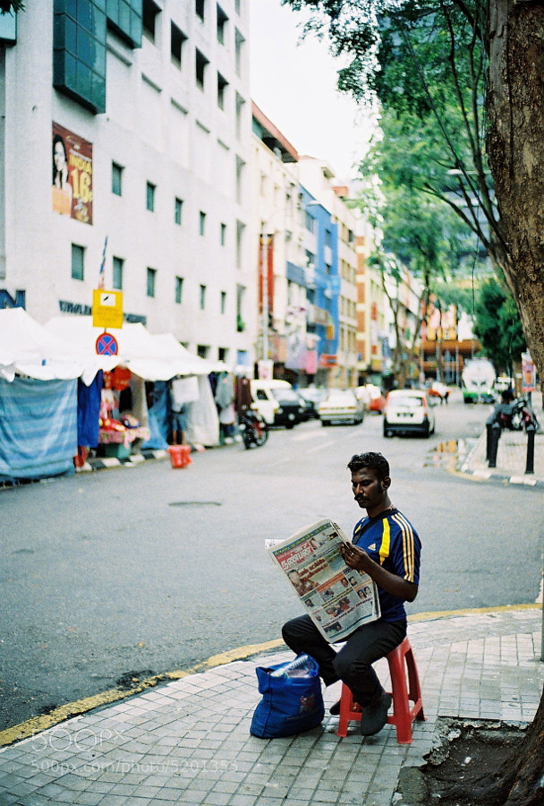 Not sure what he is doing there early morning reading newspaper at the empty roadside....i guess this is what we called street life!!! Kuala Lumpur, Malaysia.