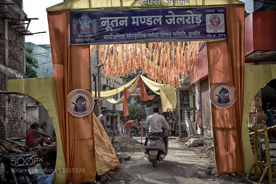 Digital HDR image of a man on a scooter passing through a decorative banner/canopy on a street in Indore, India
