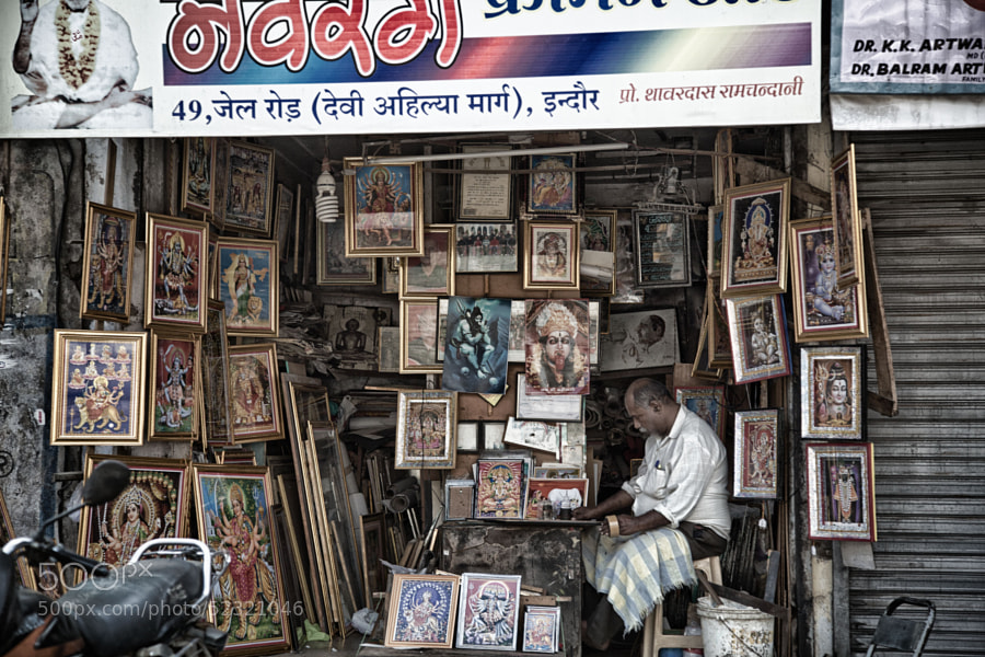 Digital HDR image of a shop-keeper at a street corner picture stand in Indore, India