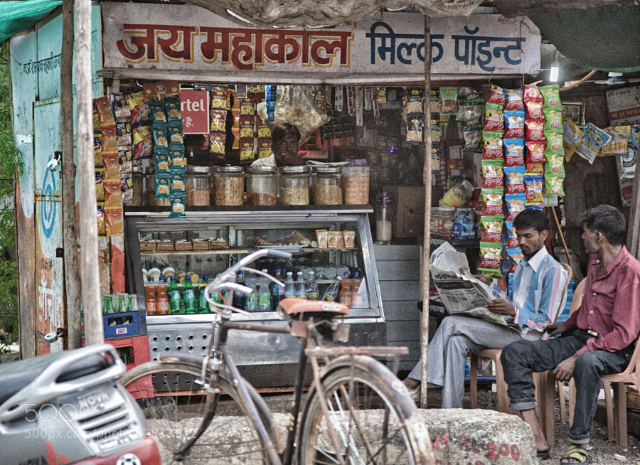 Digital color HDR image of two men sitting by a roadside snack shack in Indore, India
