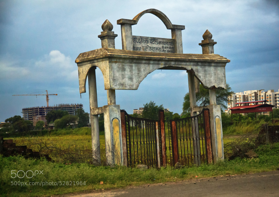 Digital color HDR image of a rusty gate and remnants of a stone entryway leading to nowhere on a field in Indore, India