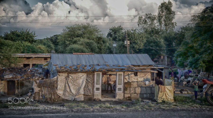 Digital HDR color image of a humble stone house on the side of a road in India