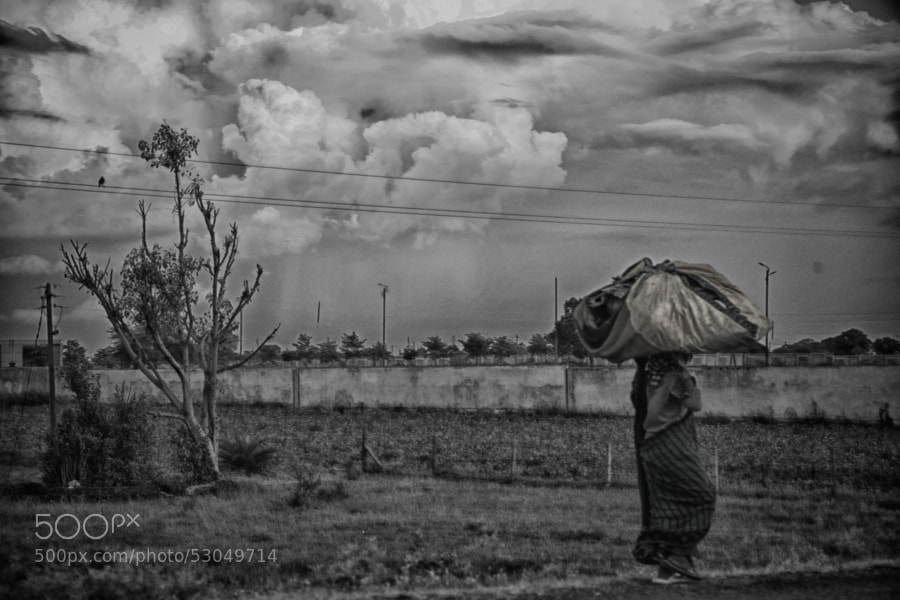 Digital b&w HDR image of a woman carrying a large sack on her head walking past a field on a cloudy evening in Indore, India