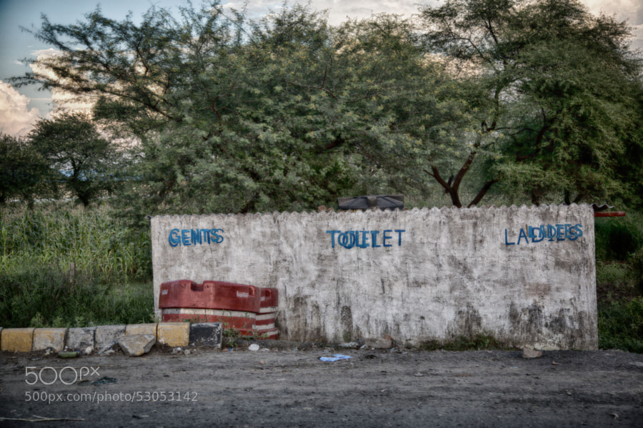 Digital color HDR image of a road-side stone wall leading into gents and ladies toilets in Indore, India