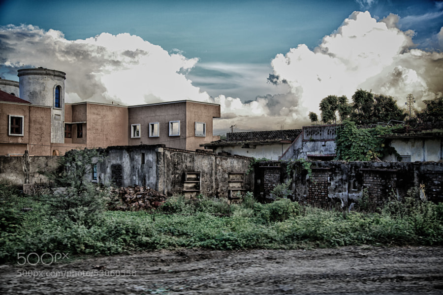 Digital color HDR image of dilapidated structures juxtaposed with new buildings on a field in India,