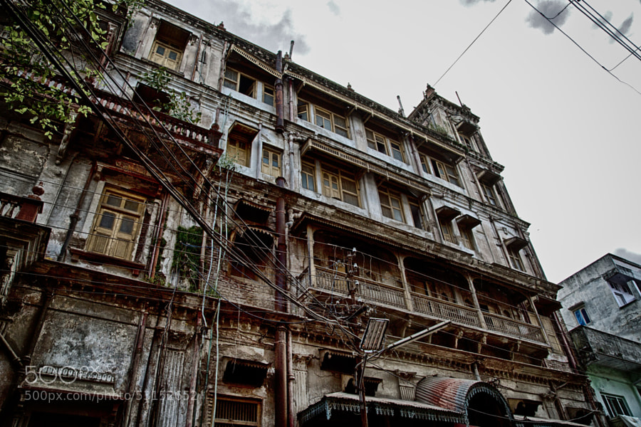 Digital color HDR image showing a large grimy, run-down building on  street corner over looking the cloth market in Indore, India.