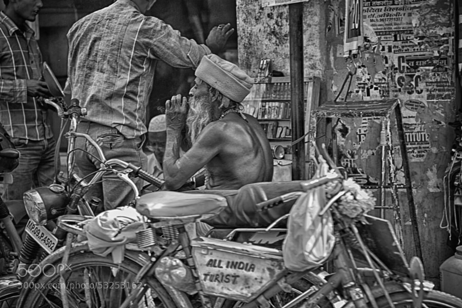 Digital b&w HDR image of an older man (topless) sitting on a motorcycle smoking something other than a cigarette in Indore, India