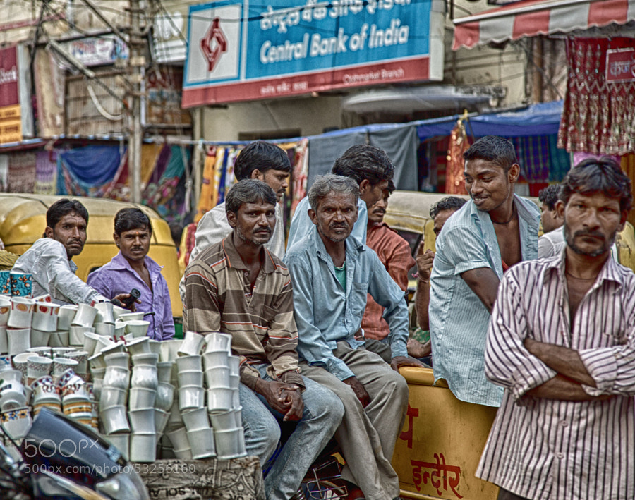 Digital color HDR image of a group of men hanging out on a cart full of coffee mugs at the market in Indore, India