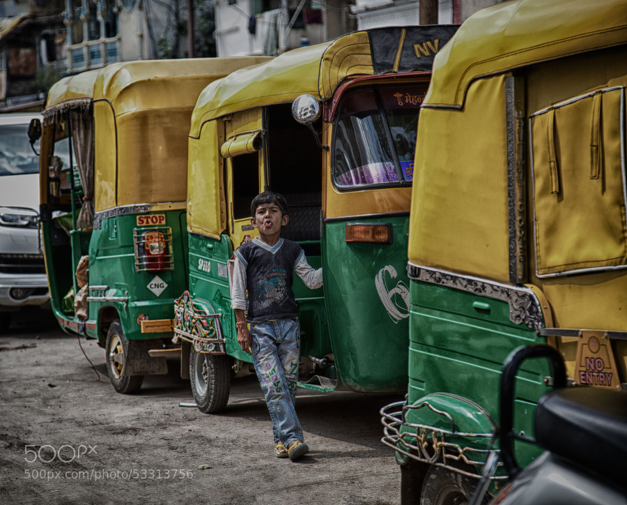 Digital color HDR image of a young boy leaning against a pedi-cab, and sticking his tongue out, on a street corner in India
