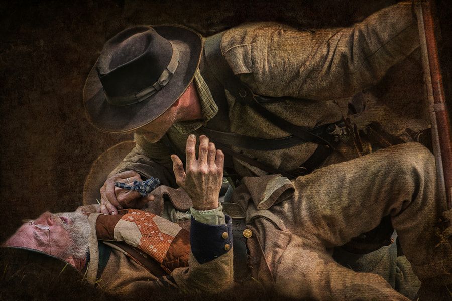 A Confederate soldier consoles a wounded comrade during Hale Farm and Village's 150th anniversary of Gettysburg re-enactment.