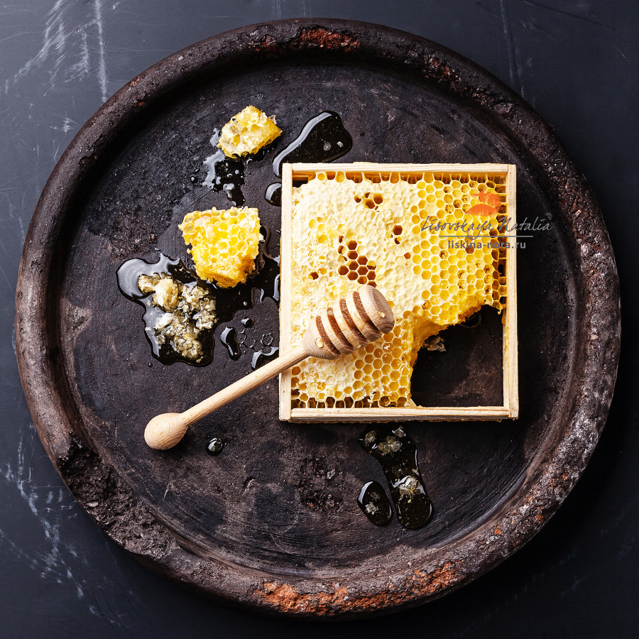 Honeycomb with wooden honey dipper on black textured background
