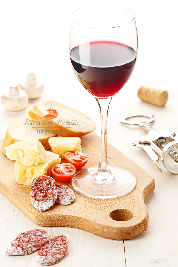 Red wine glass and assortment of snacks