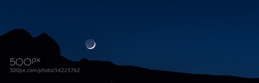 Moon disappearing behind the mountains