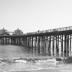 The Malibu Pier was originally built in 1905 to support the operations of Frederick Hastings Rindge's Malibu Rancho. Hides, grains, fruit, and other agricultural products were shipped from the pier either directly or by transfer to larger vessels. Building materials and other Rancho necessities arrived at the pier. The Rindge private railroad, used for freight movement within the ranch, had a terminus near the pier.  The Adamson House, located just west of the pier, included a wall built along the highway to the pier in 1932. The entrance tower and storage room, at the entrance the pier, is decorated with Malibu Potteries tile from the factory which was located just east of the pier. The tower and part of the wall are still there.  In 1934, the pier was opened to the public for pier and charter fishing. Fishermen were also shuttled back and forth from the pier and the barge Minnie A. Caine anchored a mile off shore. After the bankruptcy of Marblehead Land Co. (the Rindge's land operation) in 1936, the Malibu Pier was taken over by bondholders who had helped finance Malibu development. The pier was extended to its current 780-foot length, and the first small bait and tackle shop building was constructed at the ocean end by 1938.  During World War II, the end of the pier served as a U.S. Coast Guard daylight lookout station until an intense storm in the winter of 1943-1944. The end of the pier, including the bait and tackle shop, was destroyed and had to be rebuilt. The remains of the pier were sold to William Huber's Malibu Pier Company for $50,000 with the proviso that he would construct a building for the Coast Guard to re-occupy. After the end of the war, Huber expanded the pier and built the familiar twin buildings at the end for a bait and tackle shop plus a restaurant.  In 1960, an artificial reef was constructed in the ocean about one mile southeast of the pier in an attempt to protect it from ocean damage. The reef was composed of concrete pilings, derelict s