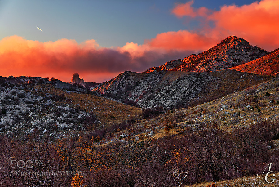 At the end of the clear winter day new clouds swarm above Velebit mountain and distant Stapina monolith