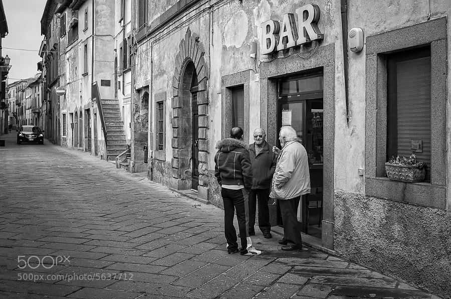Three friends have a chat outside a bar on Italian street