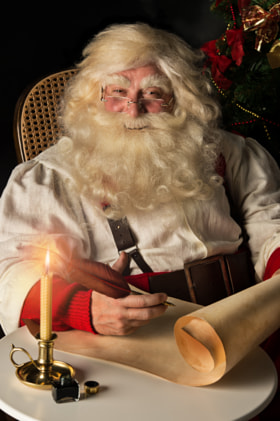 Santa Claus sitting at home and writing on old paper roll to do - stock photo
