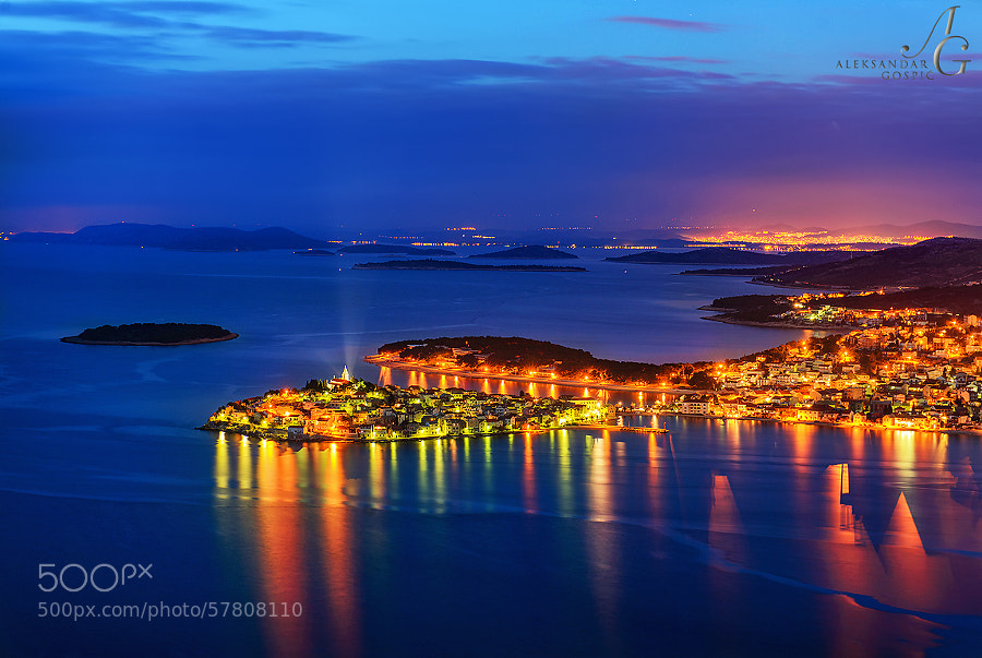 Night falls over Primošten town and the islands of Šibenik archipelago on the Croatian coast, in the distance are the lights of Šibenik city