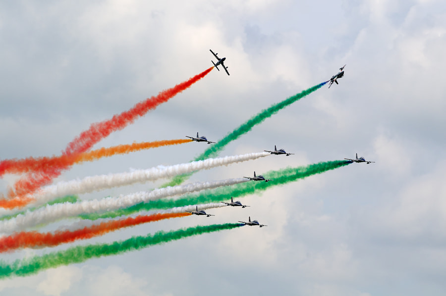 The Frecce Tricolori (Italian, literally Tricolour Arrows), officially known as the 313° Gruppo Addestramento Acrobatico, is the aerobatic demonstration team of the Italian Aeronautica Militare, based at Rivolto Air Force Base, in the north-eastern Italian region of Friuli Venezia Giulia, province of Udine. They were formed in 1961 as an Air Force team, replacing unofficial teams that had been sponsored by various commands by the end of the 1920s.  The team flies the Aermacchi MB-339-A/PAN, a two-seat fighter-trainer craft capable of 898 km/h at sea level. With ten aircraft, including nine in training and a solo, are the most numerous aerobatic team in the world, and their flight schedule, including a around twenty stunts and lasting about half an hour, has made them the most famous.  The team's official name is: 313° Gruppo Addestramento Acrobatico, Pattuglia Acrobatica Nazionale (PAN) Frecce Tricolori.  Source: Wikipedia  Best wishes,  Harry