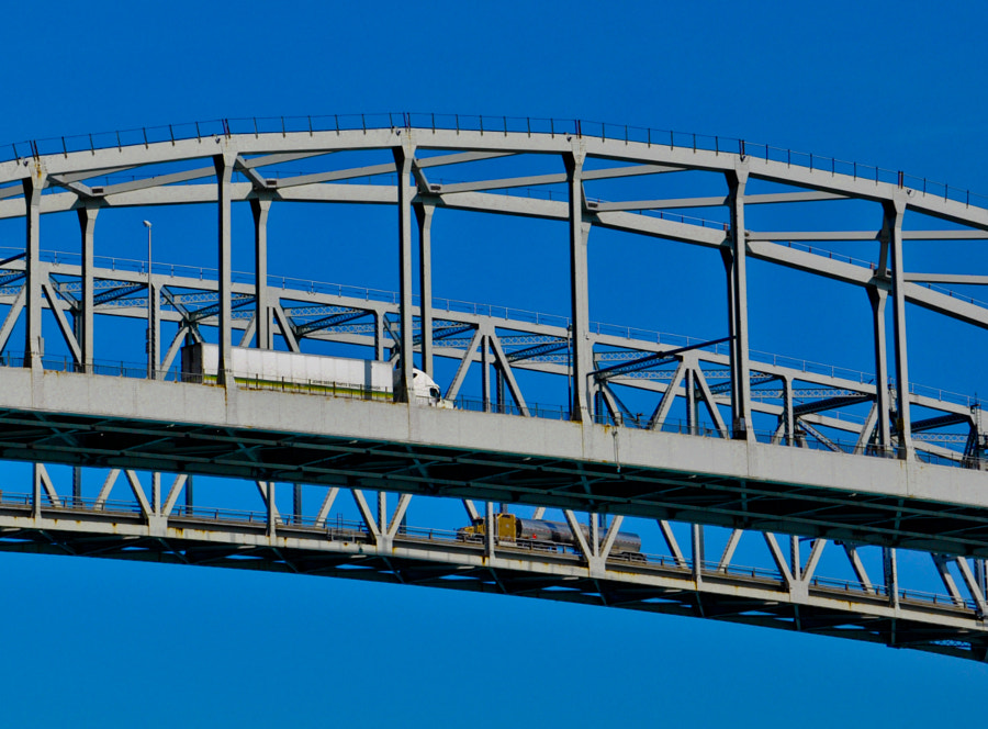 On the Blue Water Bridge, high above the St. Clair River as it empties into Lake Huron, two trucks pass each other as one heads into Canada from the USA and another into the USA from Canada.