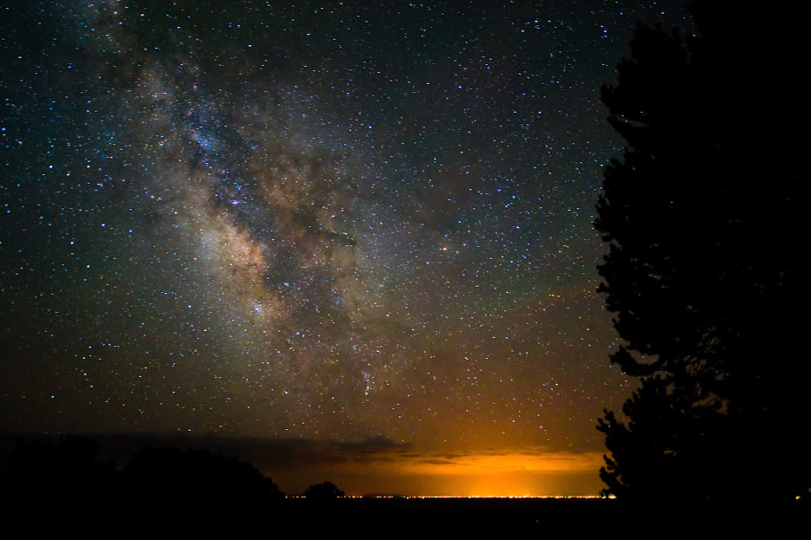 """An incredible view of the Milky Way dominates the skyline above the little mountain town of Alamosa.  This image was taken in the San Luis Valley near the town of Crestone, Colorado.  Aside from the amazing view in the sky, I wanted to mention that none of the gold color above the town comes from a sunrise or sunset.  The gold light comes entirely from the city lights of Alamosa.  Even more amazing than that though is the deep space view above the town.  As this is the last image in my series from the """"dark side"""", I would like to thank all of you for your incredible support along the way.  In the short 9 days I rented the full-frame camera and lenses, I worked my day job for 5 days, dealt with some crappy weather, and still found time to take 4 night trips into the hills totaling over 1,000 miles!  More impressive than that though are the results in the photographs themselves.  And in this direction, I will admit I am intrigued.  I'll have to wait a while to get the funds to support this line of photography, but I'm thinking my research on the """"dark side"""" has only just begun."""