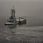 The Blue tug positions survey barge in channel below Forbes Street bridge during snow storm.