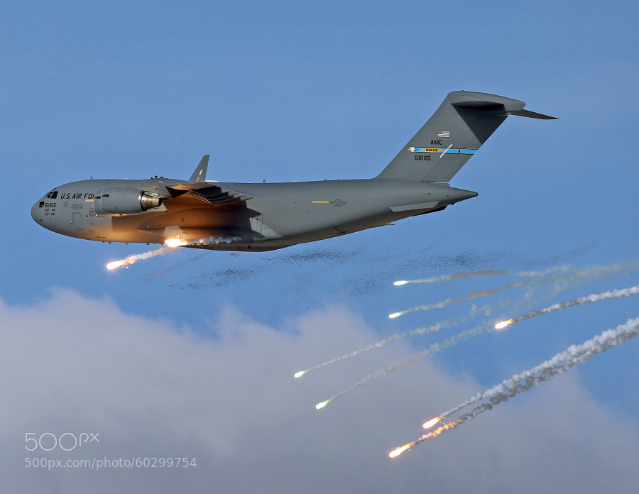 This C-17A Globemaster III is dumping Chaff and Flares to defeat any Surface to Air Missile (SAM) threats in the vicinity.