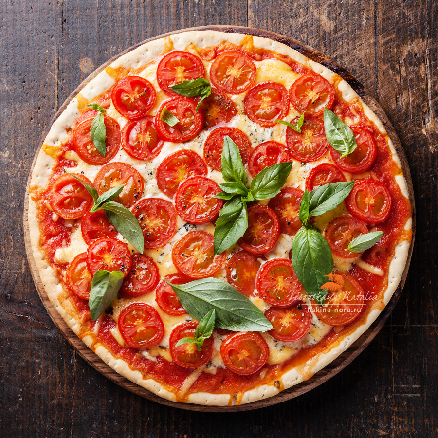 Italian pizza with cherry tomatoes and green basil on wooden table