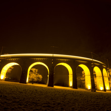 Train over Brusio viaduct in a snowing night