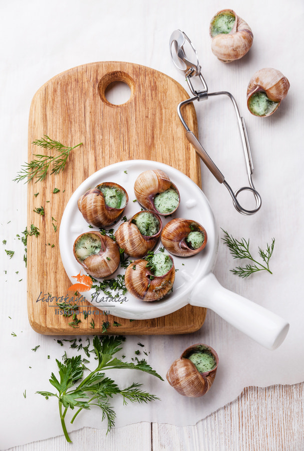 Baked snails with garlic butter sauce and fresh greens