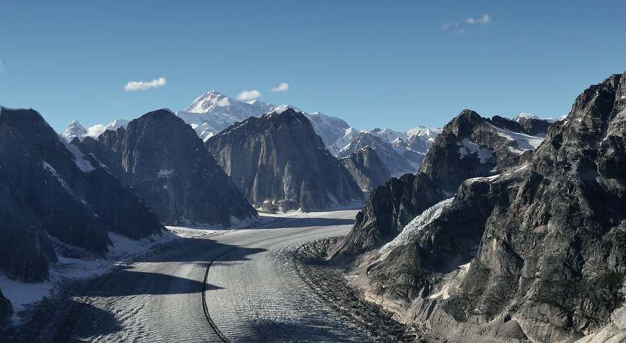 Incredibly, this is a natural 'road' carved by a glacier with Mt. McKinley in the background. This demonstrates the sheer rock-carving power of the moving ice flows.