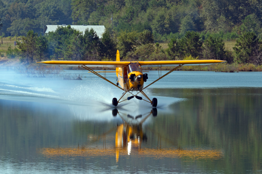 Greg Koontz skips across the pond next to his home in a clipped wing Piper Cub aircraft