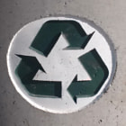 This is a recycle logo cast into cement on the side of a trash can.  Please recycle!  http://recycle.com/